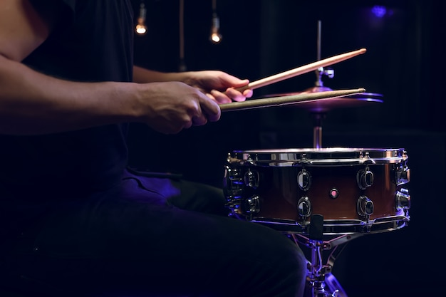 Baterista tocando baquetas em uma caixa no escuro. conceito de concerto e performance ao vivo. Foto Premium