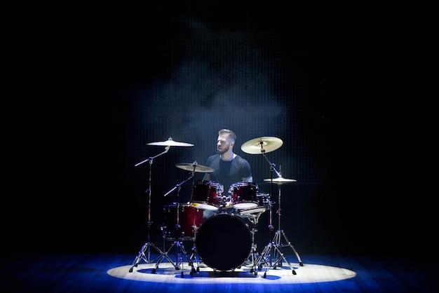 Baterista tocando bateria com fumaça e pó Foto Premium