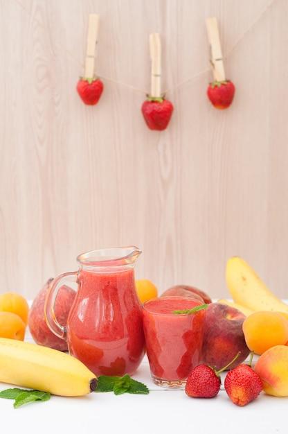 Batido de banana morango saudável com hortelã em um copo e jarra em fundo de madeira. fundo de bananas, pêssegos e damascos de frutas frescas Foto Premium