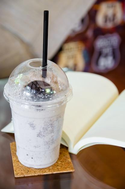 Batido de chocolate ao leite com o livro aberto na mesa de vidro Foto Premium