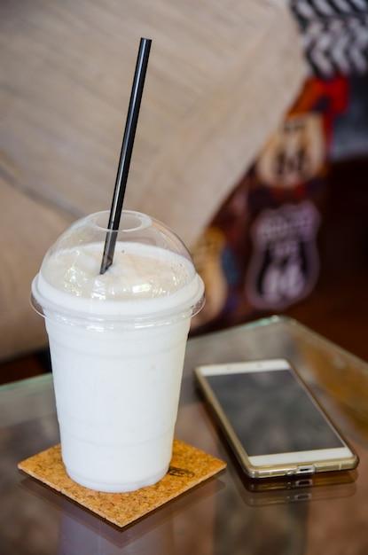 Batido de leite com smartphone na mesa de vidro Foto Premium