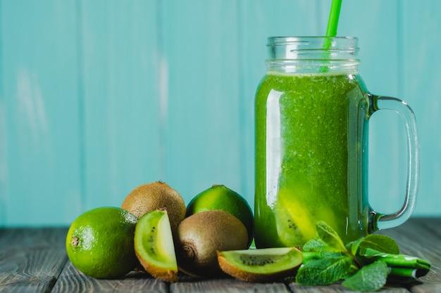 Batido verde misturado com ingredientes no foco seletivo da mesa de madeira. Foto Premium