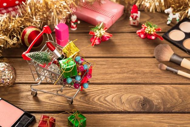 Batom no carrinho de compras, pincel de maquiagem e enfeites de natal em madeira para o fundo de natal Foto Premium