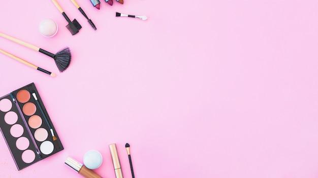 Batom; pincéis de maquiagem e paleta no fundo rosa Foto gratuita
