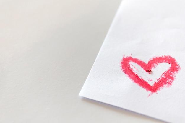 Batom rosa manchado em forma de coração no papel branco na mesa branca. Foto Premium