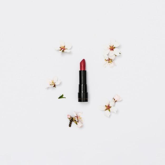 Batom vermelho com galho de flor de primavera em fundo branco Foto gratuita