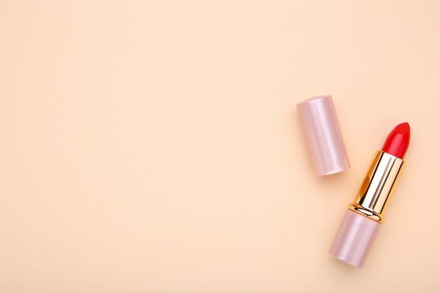 Batom vermelho sobre fundo bege, maquiagem Foto Premium