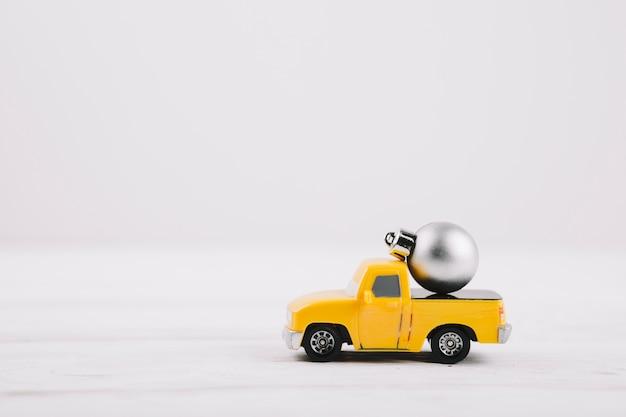 Bauble pequeno no carro de brinquedo amarelo Foto gratuita
