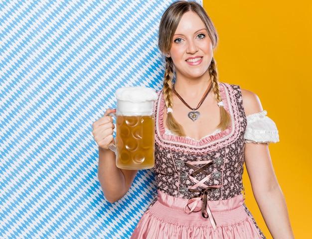 Bávara mulher segurando a caneca de cerveja Foto gratuita