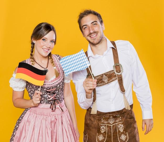 Bávaro homem e mulher segurando bandeiras Foto gratuita