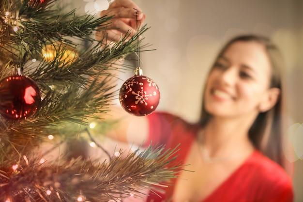 Beautful mulher fazendo a árvore de natal em casa Foto Premium