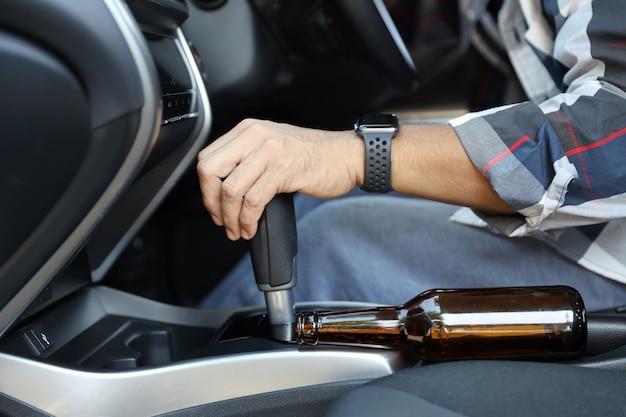 Bêbado, homem, cair, sono, enquanto, dirigindo um carro, com, garrafa álcool, ao lado Foto Premium