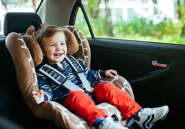 Bebé adorável em um banco de carro da segurança. Foto Premium