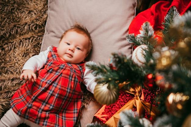 Bebê ao lado da árvore de natal Foto Premium