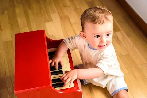 Bebê aprendendo a tocar piano com um instrumento de brinquedo de madeira, uma cena infantil tenra e engraçada. Foto Premium