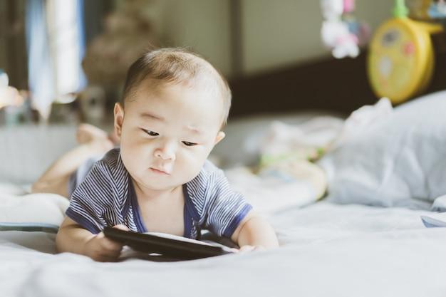 Bebê asiático está aprendendo e assistindo conteúdo e mídia social no telefone celular. Foto Premium