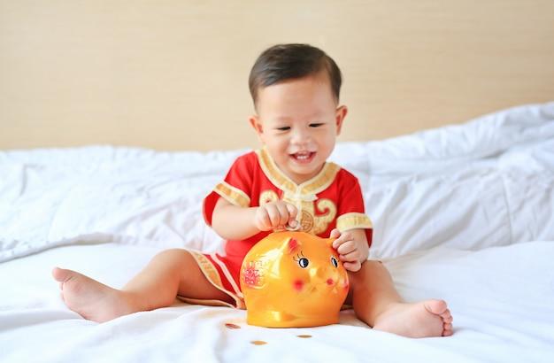 Bebé asiático pequeno de sorriso que põr algumas moedas em um banco piggy na cama. Foto Premium