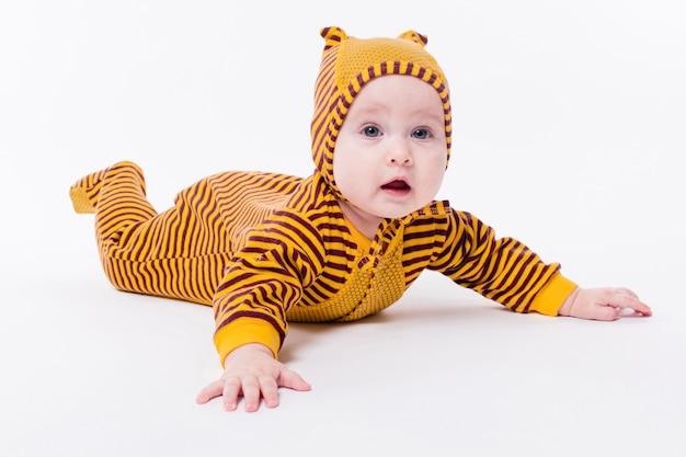 Bebé bonito que encontra-se em abelhas de um terno Foto Premium