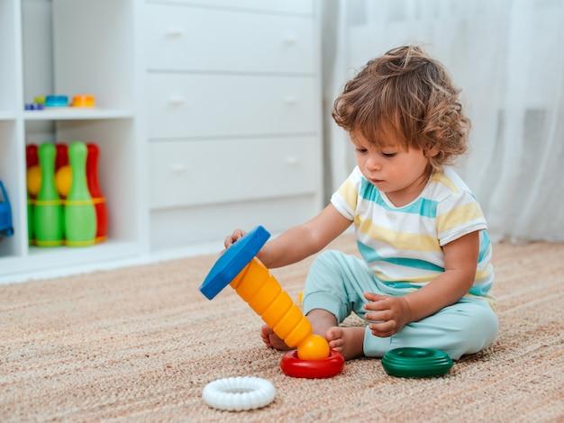 Bebê brinca no chão da sala em brinquedos plásticos educativos. Foto Premium