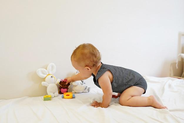 Bebê brincando. bebê brincando com brinquedos em casa, sala de luz Foto Premium