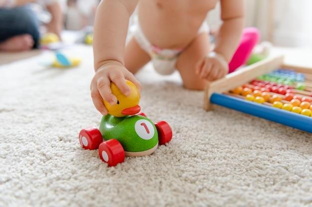 Bebê brincando com um carro de madeira Foto Premium