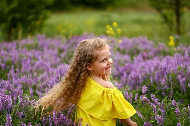 Bebê com cachos girando em um campo de lavanda, vestido com um vestido amarelo, noite de verão Foto Premium