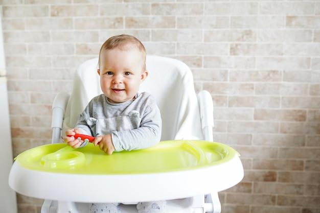 Bebê com colher na cadeira na sala de jantar, sorrindo e feliz criança. Foto Premium