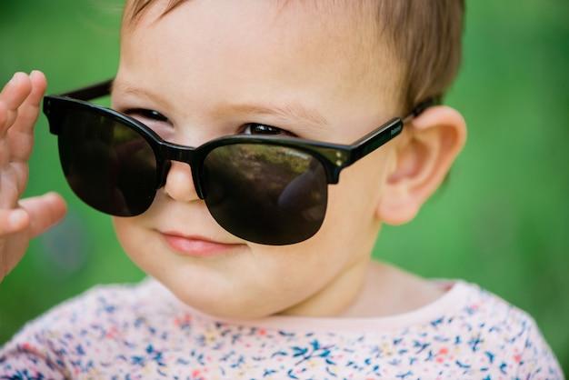 Bebê com óculos de sol na relva verde Foto Premium