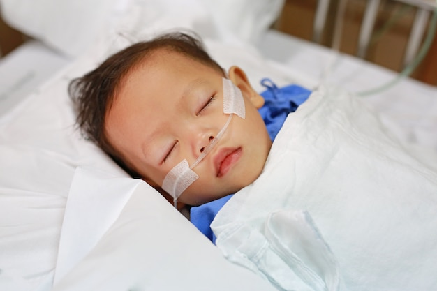 Bebé com tubo de respiração no nariz que recebe o tratamento médico. cuidados intensivos no hospital. Foto Premium