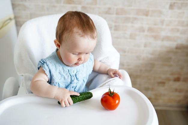 Bebê comendo legumes. pepino verde na mão da menina na cozinha ensolarada. Foto Premium
