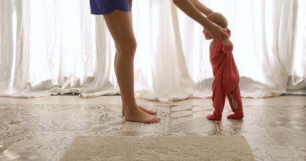 Bebê dando os primeiros passos com a ajuda da mãe Foto Premium