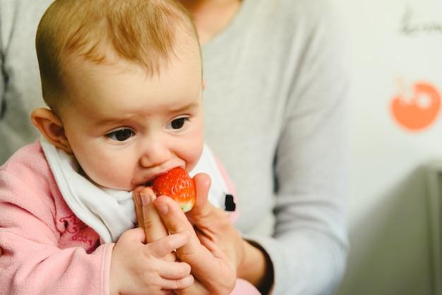 Bebé de 4 meses a começar a experimentar os primeiros alimentos utilizando a técnica de baby led weaning (blw) Foto Premium