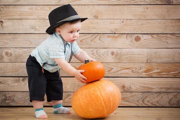 Bebê de chapéu preto com abóboras na madeira Foto Premium