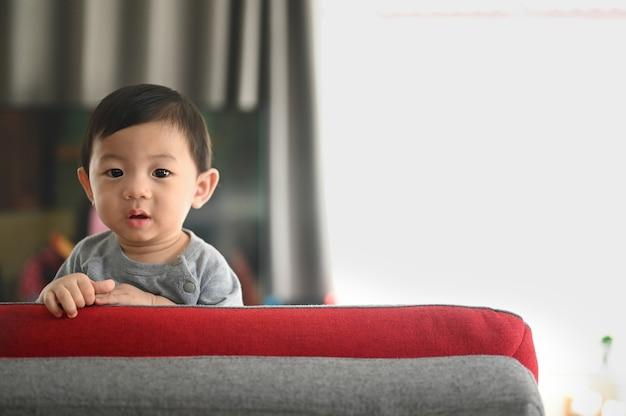 Bebê de pé em um sofá na sala de estar. Foto Premium
