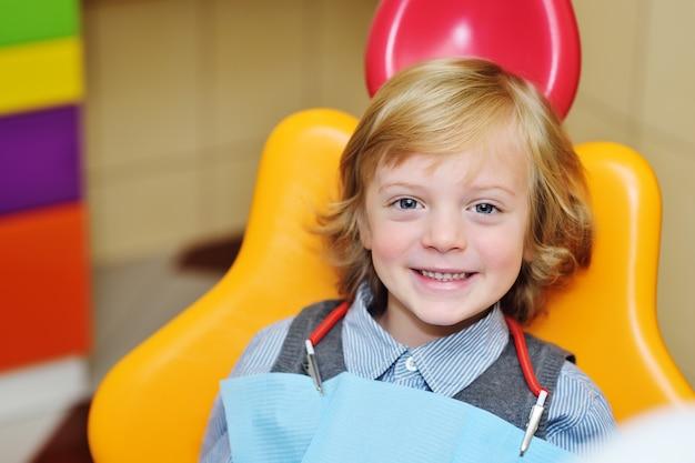 Bebé de sorriso com cabelo curly louro na cadeira dental. Foto Premium