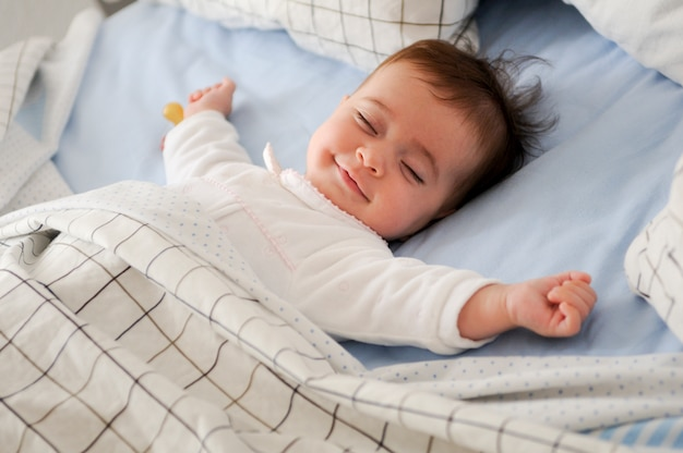 Bebê de sorriso que encontra-se em uma cama Foto gratuita