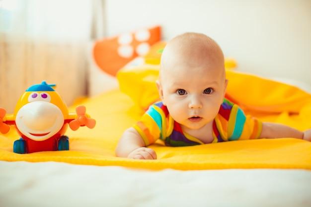 Bebê deitado em uma cama amarela Foto Premium