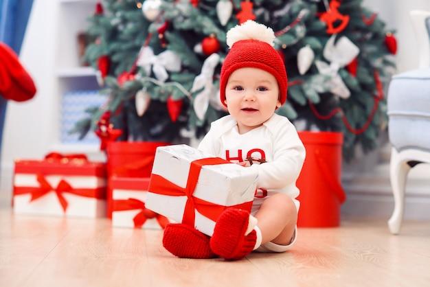 Bebê desembalar caixas de presente com decoração de natal, vestida de papai noel, luzes de bokeh, conceito de férias de inverno Foto Premium