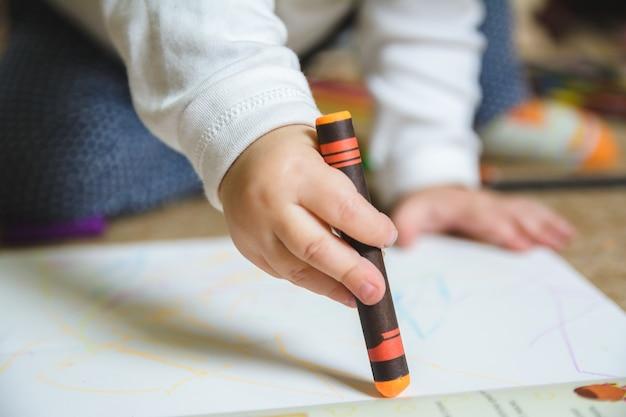 Bebê desenhando com giz de cera laranja no papel Foto gratuita