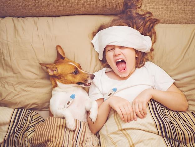 Bebé doente e cachorrinho sob a colcha Foto Premium