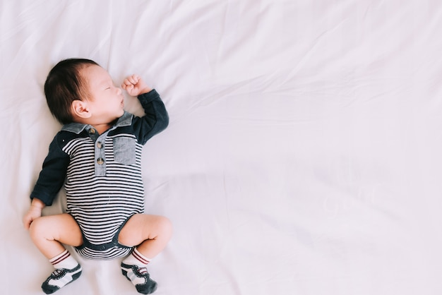 Bebê dormindo na cama branca macia no quarto - momentos felizes em família Foto Premium