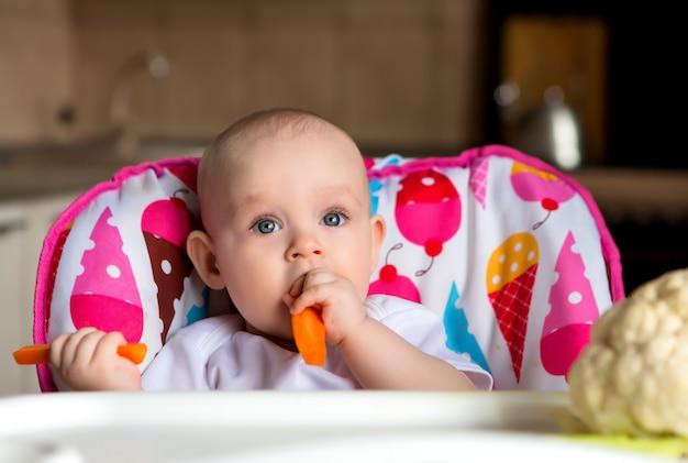 Bebê em uma cadeira de criança, comer legumes Foto Premium