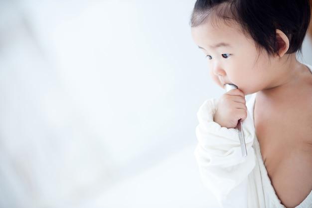 Bebê está comendo sua comida de bebê em uma mesa branca. Foto Premium