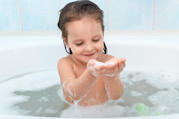 Bebê feliz encantador tomando banho, brincando com bolhas de espuma alegremente. Foto gratuita