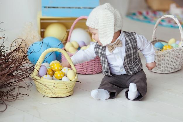 Bebê feliz engraçado no chapéu, no laço do laço e no terno jogando com ovos da páscoa. Foto gratuita