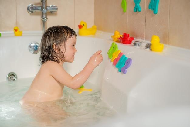 Bebê feliz no banheiro brincando com bolhas de espuma e letras. higiene e cuidados para crianças pequenas. Foto Premium