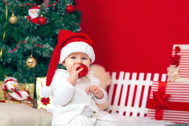 Bebê feliz no interior de natal, boné de papai noel com presentes Foto Premium