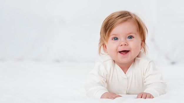 Bebê feliz posando com espaço de cópia Foto gratuita