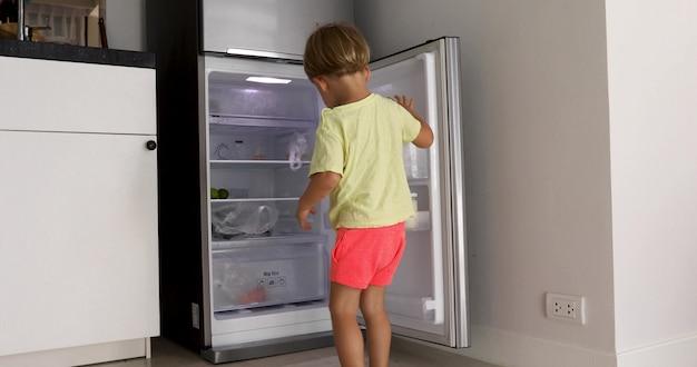 Bebê fofo abre geladeira parece garrafa Foto Premium