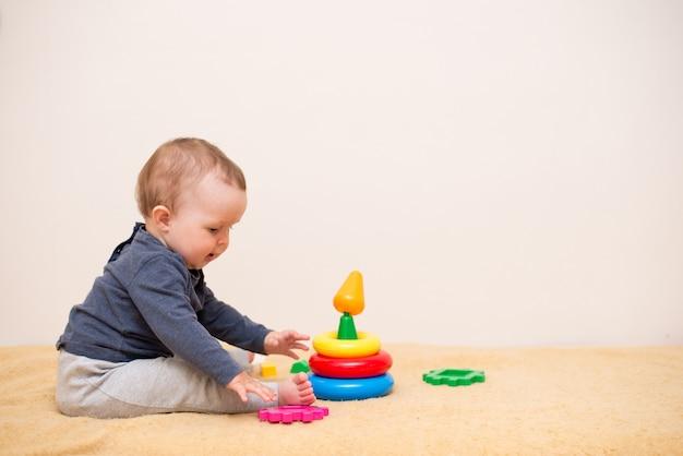 Bebê fofo brincando com pirâmide de brinquedo colorido no quarto de luz. Foto Premium